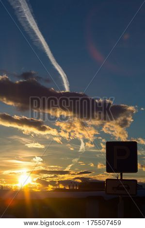 Sunset with sun rays, colourful dark clouds and the plane trace in winter.