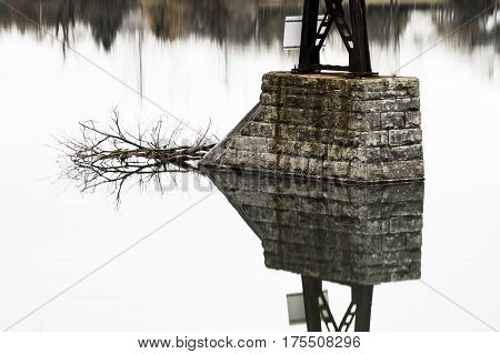 Mirrored reflection in perfect symmetry of bridge stone pillar and fallen branch on calm smooth lake