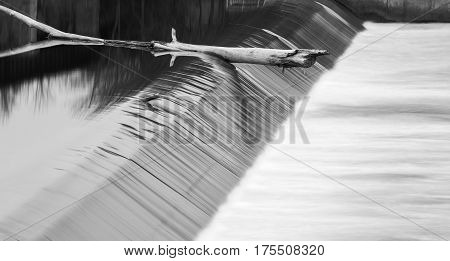 Large tree branch caught on the edge of a water dam relfections and smooth current flowing in black and white