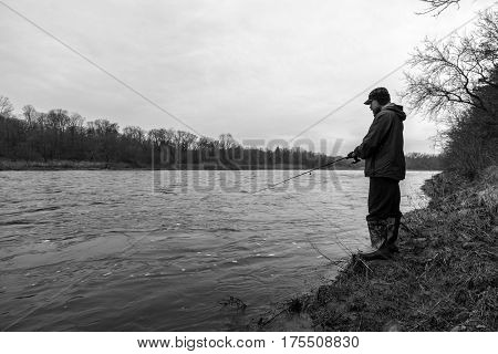 Rugged outdoors fisherman standing on bank of fast flowing river fishing black and white scene