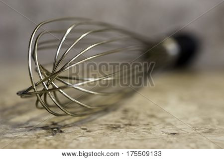 Closeup of whisk with black handle lying on marbled kitchen counter cooking concept