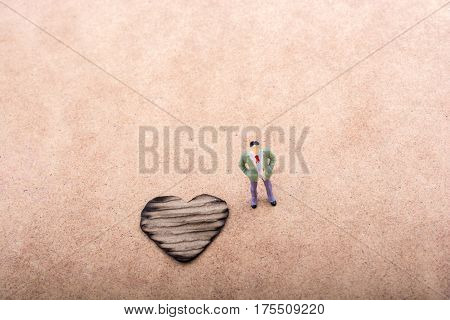 Figurine And Heart Shaped Burnt Out Of A Cardboard