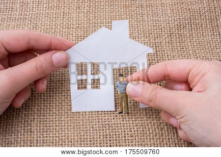 Paper House And A Man Figurine On A Canvas Background