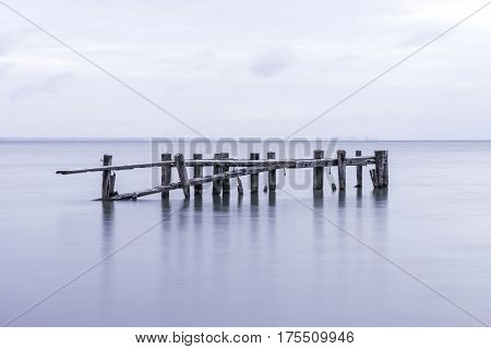 Old pier structure falling down posts standing in tranquil lake waters