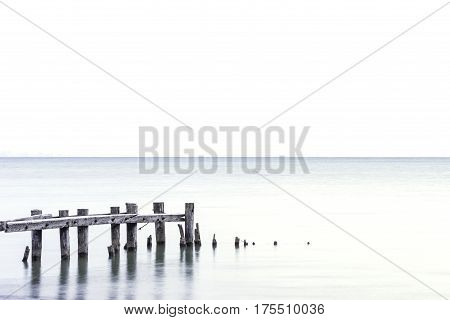 Posts of broken pier standing in a light blue lake white sky background room for text