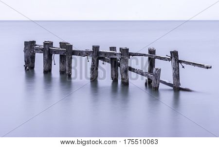 Old broken pier with weathered posts standing in tranquil calm sea water simple seascape poster