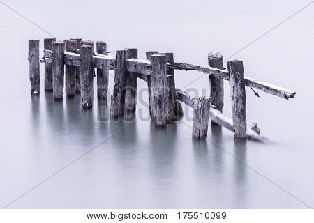Broken down old pier posts in calm water covered with light dusting of snow