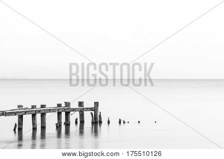 Seascape tranquil background with room for text rustic pier posts in lower left of water