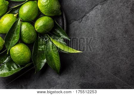 Green lemon Lime with fresh leaves on black plate, slate background. Top view