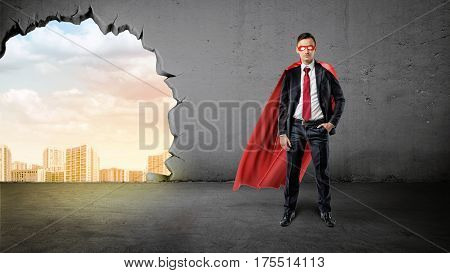 A businessman in a hero red cape with a hand in his pocket on concrete background with a hole to the city view. Business and success. Personal qualities. Working to win.