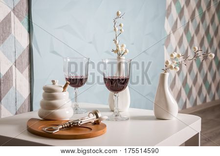 Red wine , wine glass, corkscrew. white table, wooden plate and two modern vases. modern decoration.