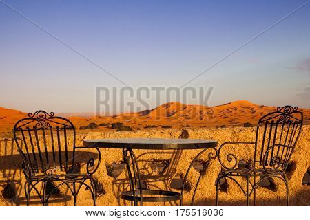 Table and chair on hotel roof top terrace in Sahara desert,  Morocco