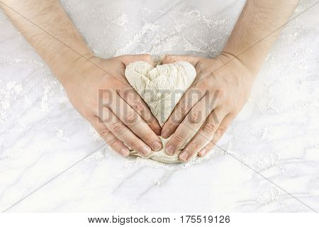 A man's hands kneading dough in the form of a heart, with flour on a marble table, with a place for text