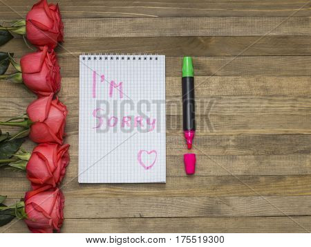I'm sorry phrase on notebook and rose bouquet