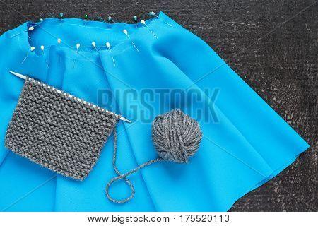 Grey knitting and blue needlework on black background.