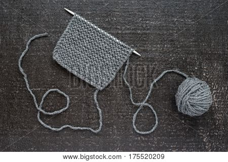 Piece of grey knitting on a kneeting needle on black background. Shot from above.