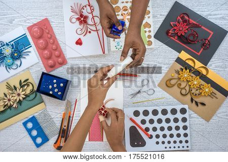 paperquilling art work. two multi-cultural female hands desinging paper quilling handycraft seen from top