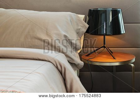 Modern Black Lamp And Brown Pillow On Bed