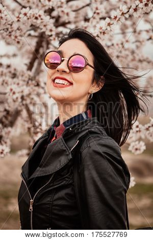 Brunette girl near a almond tree with many flowers