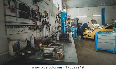 Mechanic in the garage, car preparing for repairing, wide angle, wide angle