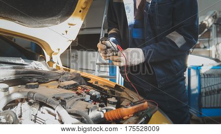 Mechanic works with voltmeter - car electrics - electrical wiring, close up