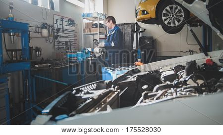Mechanic in the garage, car preparing for professional diagnostics, wide angle