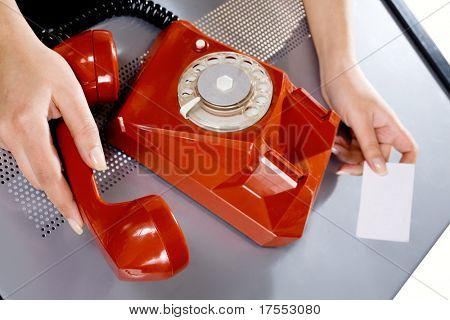 Woman holding business card and dialing on red phone