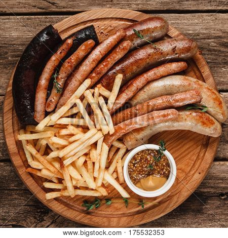 Oktoberfest traditional menu, German food. Tasty grilled sausages with crispy french fries and sauce, top view.