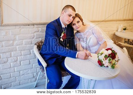 Wedding Couple Sitting At A Table In A Cafe And Holding Hands.