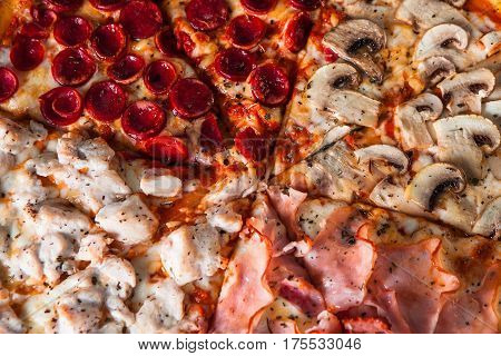Yummy baked pizza with mushrooms, ham, chicken and sausages, close up view. Restaurant menu photo, appetizing food background.