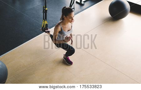 Sportive woman exercising in gym with stretching bands