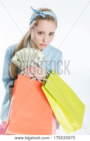 Sad young woman holding shopping bags and dollar banknotes on white