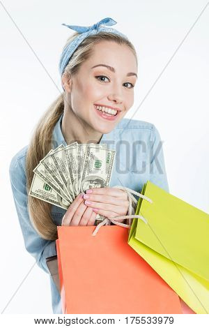 Happy young woman holding shopping bags and dollar banknotes on white