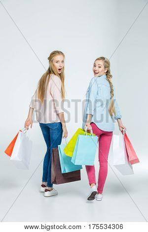 Surprised young women with shopping bags looking over shoulders