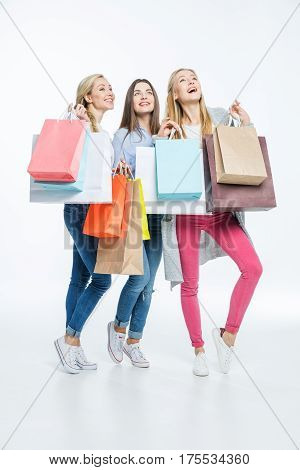 Full length portrait of three excited young women with shopping bags
