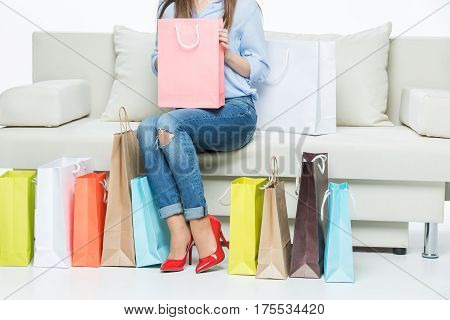 Partial view of young woman sitting on sofa with pink shopping bag