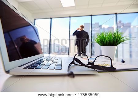 Businessman at the window outside focus in  office. Laptop, glasses documents and pen  workplace on  desk.