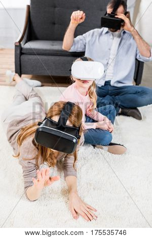 Family with one child using virtual reality headsets at home