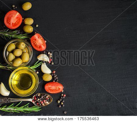Top View Of Olive Oil And Ingredients For A Healthy Vegetarian Salad - Cherry Tomatoes, Olives, Garl