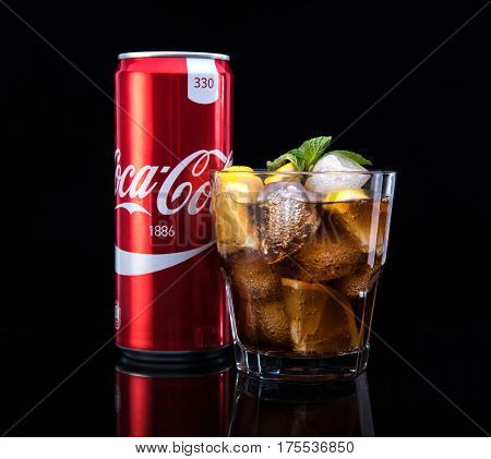 MINSK, BELARUS - JANUARY 05, 2017: Editorial photo can and glass of Coca-Cola with ice on dark background. Coca-Cola is a carbonated soft drink sold throughout the world.