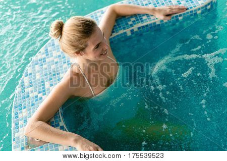 Woman Relaxing In Pool And Smiling