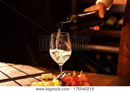 Hand holding a bottle of wine and pouring wine into a glass. Wine vault.