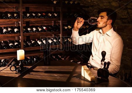 The man is tasting wine from a wine glass. Man sitting by the table in a wine vault.