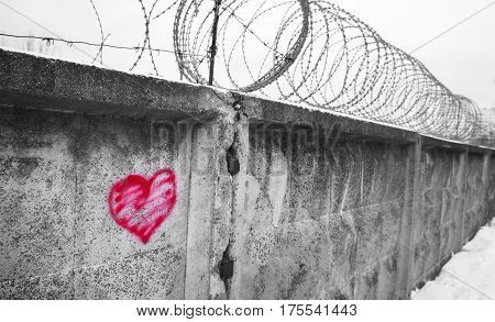 red heart painted on a concrete wall, against the backdrop of barbed wire, the concept of prison, salvation, Refugee, Silent,  lonely, broken love, relationship, lonely, obstacle,  platonic one sided