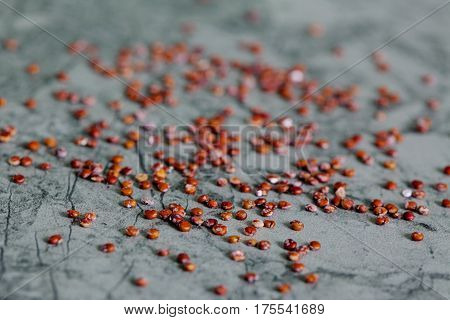 red quinoa grain spread on green background with backlight - top view