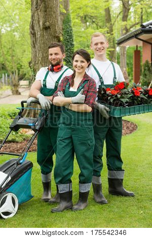 Happy Gardeners With Plants And Lawn Mower