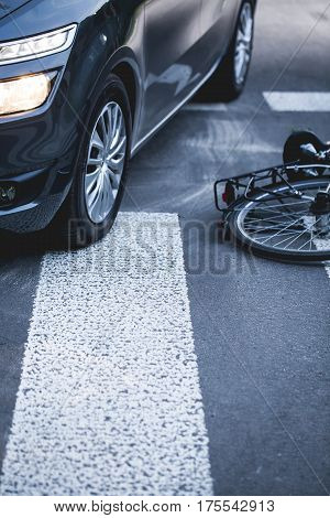 Bike lying next to a car on the pedestrian crossing after accident