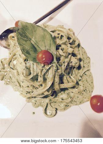 Italian Green pesto and basil tagliatelle pasta served on a white plate