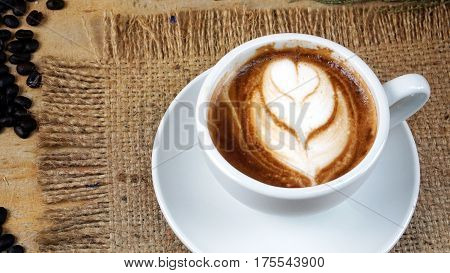 Cappuccino coffee. A cup of latte, cappuccino or espresso coffee with milk put on a wood table with dark roasting coffee beans. Drawing tulips flower by foam milk on top.