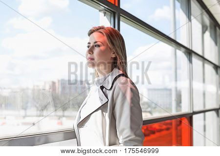 Young businesswoman looking through glass at railroad station